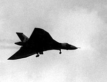 A delta-winged aircraft silhouetted against the sky. It has its landing wheels down.