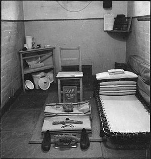 "HM Prison Wakefield - 1944: ""A view of an inmate's cell at Wakefield Prison. Clearly visible are the bed, a chair, several small shelves, and slop bucket. The rest of the inmate's belongings, such as a pair of shoes and a comb, have been set out neatly, ready for inspection. Chalked on a small blackboard are the words 'soap please'."""
