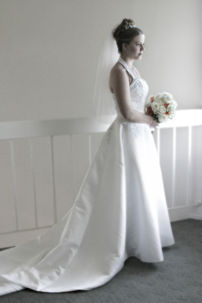 A bride in a very traditional long white wedding dress with train, tiara and white veil.
