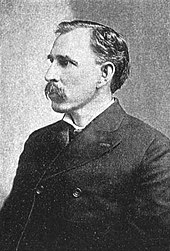 A man in his late forties with black hair and a mustache. He is wearing a tightly-buttoned black coat and facing left.
