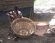 A woman weaves a basket near Lake Ossa, Littoral Province. Cameroonians practice such handicrafts throughout the country.