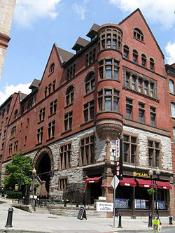 A five-story building with a lower section in stone and the upper section in brick. It has decorated windows, a tower on the corner, and a pointed roof. At the street below it is a glass-faced section with signs identifying it as the Pearl Street Pub.