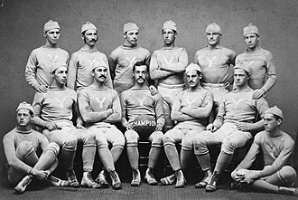 Early history of American football - 1876 Yale Bulldogs, national champions. Walter Camp is standing with arms crossed. Gene Baker is seated with the football.
