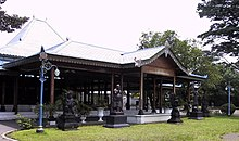 Brown wood pavilion with statues