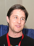 A middle aged caucasian male looks slightly to the right with a small smile. He has short brown hair and is wearing a black t-shirt with a red lanyard around his neck