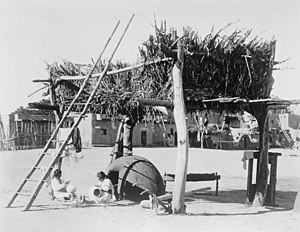 Puebloans - A Zuni drying platform for maize and other foods, with two women crafting pottery beneath it. From the Panama-California Exposition, San Diego, California. January 1915.