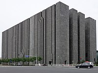 A dark gray block-like building towering over an intersection, with narrow, sometimes diagonal cracks in one side and large gaps in the other