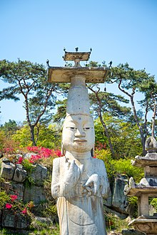 Outdoor, white, Asian statue with tall hat.