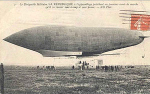 Postcard with orange stamp (French) affixed shows left flank of an airship just above the ground; some people are on the ground below the airship