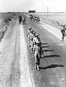 Soldiers marching on a road through an arid area