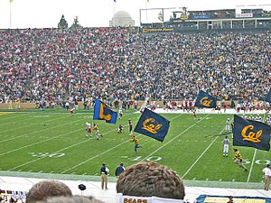 UC Rally Committee running Cal flags across the Memorial Stadium field at the 2002 Big Game. (Note the Stanford visitors section on the left and the UC Berkeley alumni section on the right.)