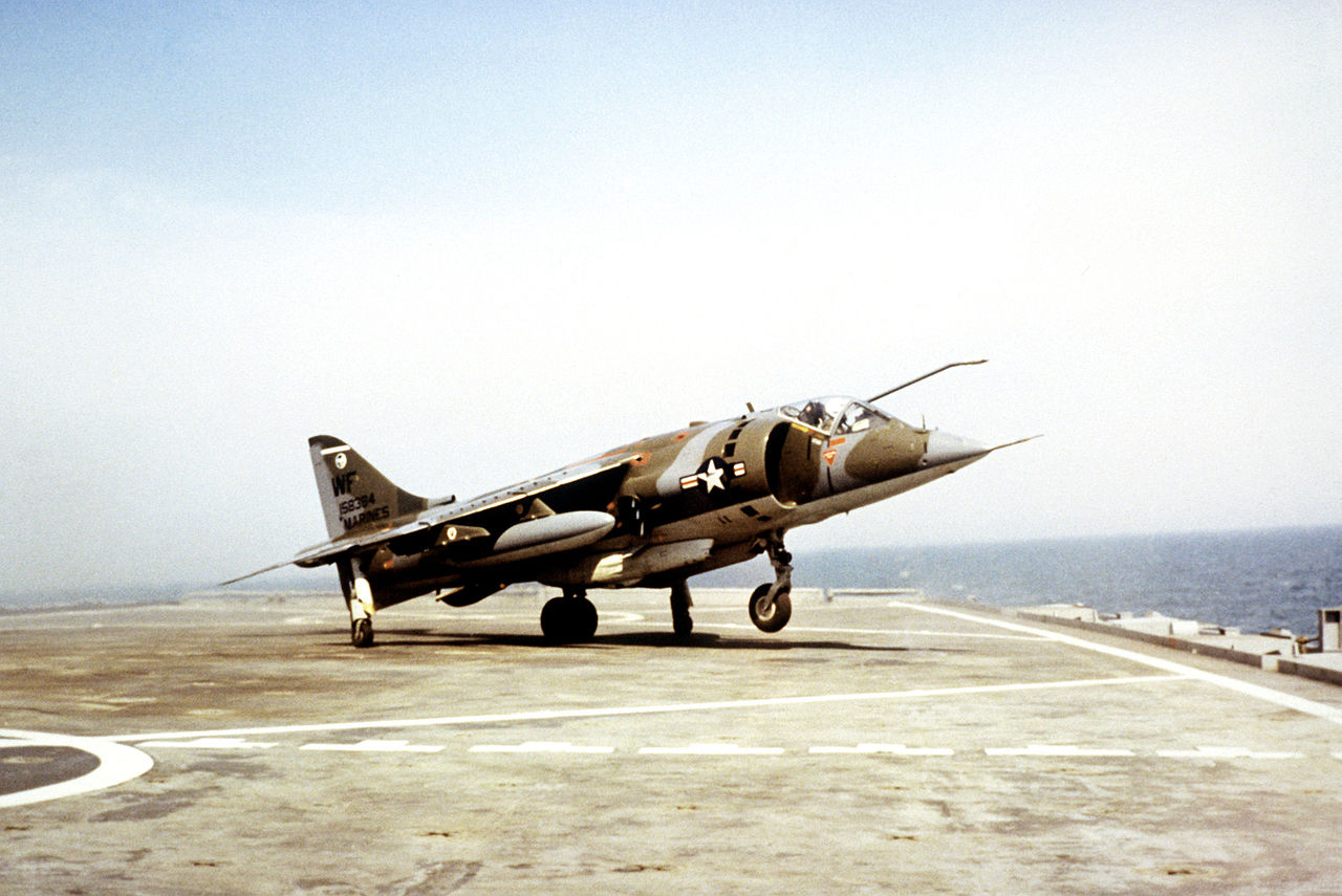 A Harrier on the deck of a small aircraft carrier, with its nose wheel off the deck