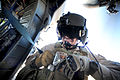 A door gunner puts on his gunner's belt, a protective device that secures him inside a HH-60 helicopter.jpg