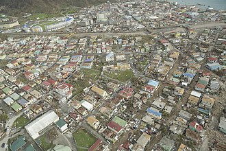 Hurricane Maria - An aerial view of part of Roseau, revealing widespread damage to roofs. Flash floods clogged roads with debris – vegetative and structural – and mud.