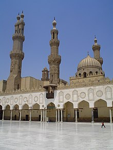 A paved courtyard is visible in the foreground, and behind it a wall of angular keel-shaped arched bays supported by columns. Behind the wall, two minarets, a dome, and another minaret are visible from left to right. In the far background in the center the top of another minaret can be seen.
