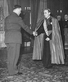 een man in aartsbisschoppelijk gewaad groet een man in militair uniform