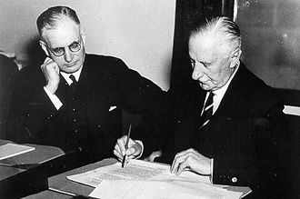 Commander-in-chief - Governor General The Lord Gowrie (right) signing the declaration of war against Japan with Prime Minister John Curtin (left) looking on. (8 December 1941)
