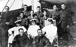 A group portrait of ten soldiers and three sailors on board a ship.