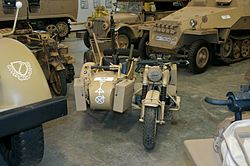 Located in a museum among other vehcicles, a front view of a desert camouflage BMW R75 motorcycle and sidecar