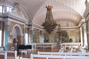 Photograph of a Baroque interior of a hall in Palace, with stucco ceiling and a large chandelier hanging from it, all in light colours