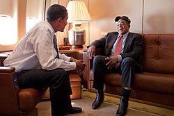 Fotografie a lui Mays într-un costum și o șapcă de baseball așezată pe o canapea în fața președintelui Barack Obama în așteptare cu o cămașă de rochie și pantaloni de costum;  ferestrele avionului sunt vizibile în stânga lor