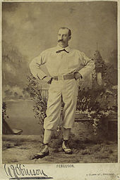 A portrait of man in a baseball uniform, standing with his hand on his hips, facing slightly to the right and up.