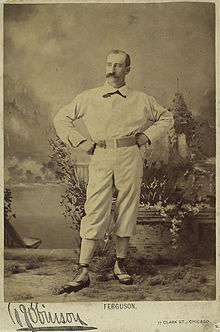 A sepia-toned photograph of a man in an old-style white baseball uniform standing with arms akimbo