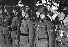 uma fotografia em preto e branco de uma linha de soldados da Waffen-SS em desfile