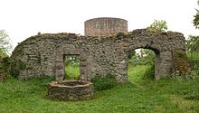 Photo of a ruined stone walls and a circular tower in a meadow