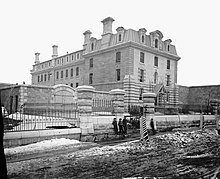 Black and white photo of a courthouse building with boys standing in the foreground