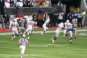 A referee (foreground) follows the action of a play between the Texas Longhorns  and the Rice Owls.