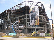 Photo de la structure du Consol Energy Center pendant sa construction ; une affiche géante représentant Sidney Crosby y est accrochée.