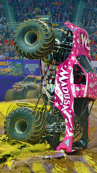 "Madusa - Miceli's monster truck, ""Madusa"", at Monster Jam in the Edward Jones Dome. The truck is stopped, balanced on its rear end"