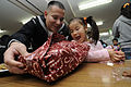 Defense.gov News Photo 101222-N-9094S-062 - U.S. Navy Petty Officer 1st Class Oscar Bernuy left with the 7th Fleet helps an orphan open her gift at the Shunko Gakuen Boys and Girls Home at.jpg