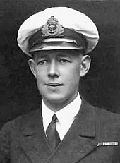 Formal head-and-shoulders portrait of young man in winter naval uniform with peaked cap