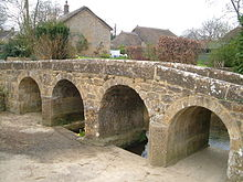 Stone bridge with four arches and low parapet.