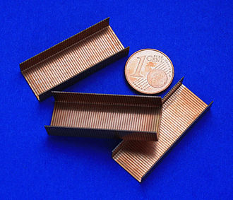 Staple (fastener) - Staple strips used in modern staplers, with a coin for size comparison.