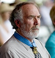 Profile of a white man with a full, gray beard wearing a star-shaped medal from a blue ribbon around his neck.