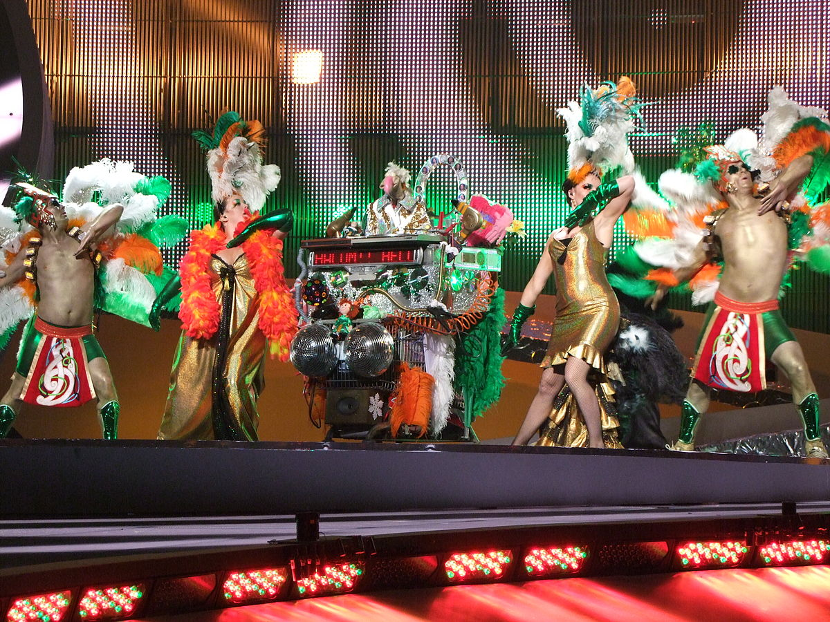 A turkey handpuppet surrounded by dancers dressed as turkeys, singing about winning Eurovision