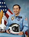 man in fight suit holding helmet, space shuttle model and American flag in background