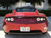 "Photograph of a parking space with the words ""SpaceX"" and ""reserved"". The parking space contains a red convertible sports car with Californian license plate TSLA 10. On the rear of the vehicle are written the words ""Tesla Roadster Sport""."