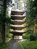 A five-storied wooden pagoda in a forest.