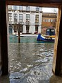 Flooded pavement and canal through a doorway in Venice in December.jpg