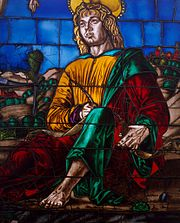 Detail of a stained glass window depicting a saint dressed in yellow, green and red robes, holding a quill.