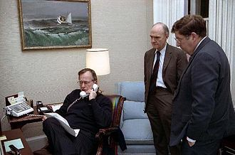 White House Chief of Staff - President George H. W. Bush sits at his desk in the Oval Office Study and talks on the telephone regarding Operation Just Cause, as Chief of Staff John Sununu and National Security Advisor Brent Scowcroft stand nearby (December 20, 1989).