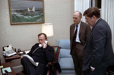 Bush speaks on the telephone regarding Operation Just Cause as General Brent Scowcroft and Chief of Staff John H. Sununu look on, 1989 George H. W. Bush on telephone.jpg