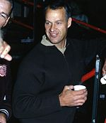 A young man is shown from the hips up.  He is dressed in black, smiling, and holding a cup in his left hand.
