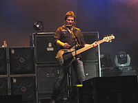A bassist is onstage with a number of large speaker cabinets.