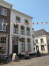 foto van Huis op de hoek van de Hamstraat, met gepleisterde lijstgevel, waarin ingangspartij met fraai bovenlicht uit ca. 1800 en kuiven van stuc boven de segmentbogen der vensters. Nog geheel woonhuis