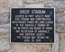 "Set against a natural stone wall, a black plaque with silver text reads, ""Greer Stadium. Located in Fort Negley Park this stadium was constructed with private funds on land leased to the Nashville Sounds by the Metropolitan Board of Parks and Recreation of Nashville and Davidson County. The stadium was opened on April 25, 1978."